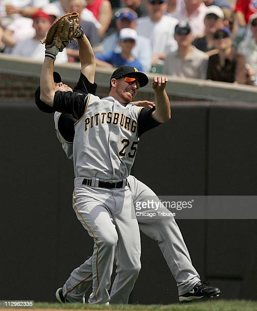 Pittsburgh Pirates first baseman Adam LaRoche collides with second baseman Freddy Sanchez while holding on to a pop fly from Chicago Cubs' Derrek Lee...