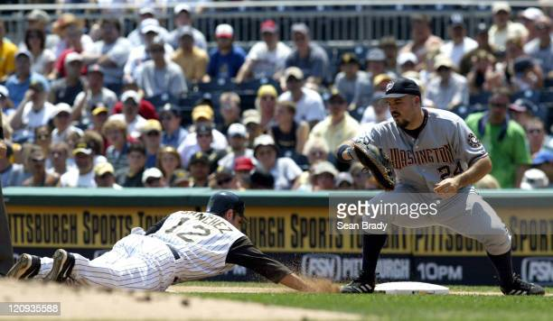 Pittsburgh Pirates Freddy Sanchez dives back to first base to beat the tag by Washington Nationals Nick Johnson during action at PNC Park in...