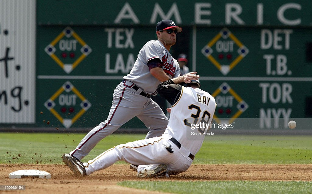 Pittsburgh Pirates Jason Bay slides safely into second base as Atlanta's Marcus Giles attempts to grab the ball during action at PNC Park in Pittsburgh, Pennsylvania on August 3, 2006.
