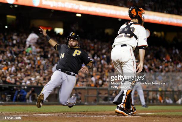 Pittsburgh Pirates' Pedro Alvarez scores on a sacrifice fly by Gaby Sanchez as San Francisco Giants catcher Buster Posey looks on in the fifth inning...