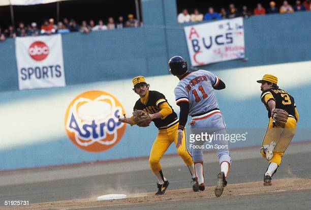 Pittsburgh Pirates' Phil Garner runs and watches while second baseman Tim Foli prepares to throw to first for a double play against Baltimore...