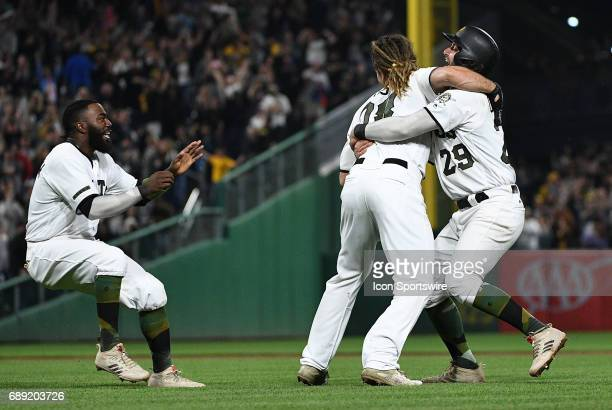 Pittsburgh Pirates right fielder John Jaso is greeted by catcher Francisco Cervelli and third baseman Josh Harrison after hitting a walkoff single in...