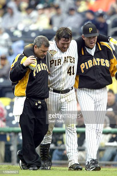 Pittsburgh Pirates Ryan Doumit is helped off the field by trainer Brad Henderson and Manager Jim Tracy after pulling a hamstring running to first...