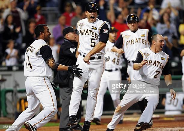 Pittsburgh Pirates' second baseman Jose Castillo shortstop Jack Wilson and other players rush in to celebrate as third baseman Joe Randa crosses the...