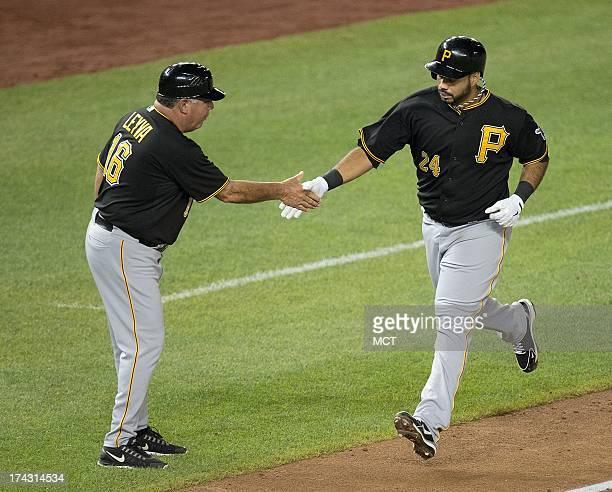 Pittsburgh Pirates third baseman Pedro Alvarez slaps hands with third base coach Nick Leyva after hitting a home run against the Washington Nationals...