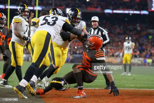 Pittsburgh Steelers center Maurkice Pouncey and Pittsburgh Steelers offensive guard David DeCastro take down Cleveland Browns defensive end Myles...
