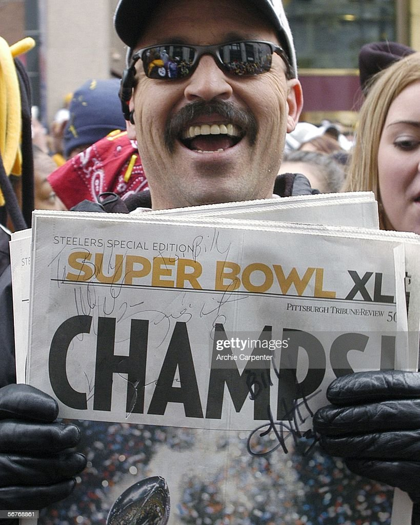 A Pittsburgh Steelers fan holds a newspaper with autographs during the victory parade celebrating winning Super Bowl XL February 7, 2006 in downtown Pittsburgh Pennsylvania.