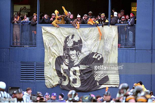 Pittsburgh Steelers fans wave Terrible Towels and cheer while standing near a banner depicting former Steelers linebacker Jack Lambert during a game...