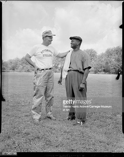 Pittsburgh Steelers football team coach 'Buddy' Parker posed with hand on shoulder of trainer Wallace 'Boots' Lewis on athletic field at Slippery...