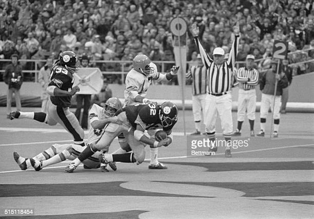 Pittsburgh Steelers' Franco Harris carries Cincinnati Bengals' Tom Casanova over the goal line during the fourth quarter as Steelers' John Fuqua and...