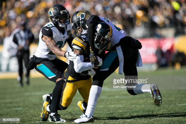 Pittsburgh Steelers wide receiver Antonio Brown fights for extra yards while being tackled by Jacksonville Jaguars cornerback Jalen Ramsey and...