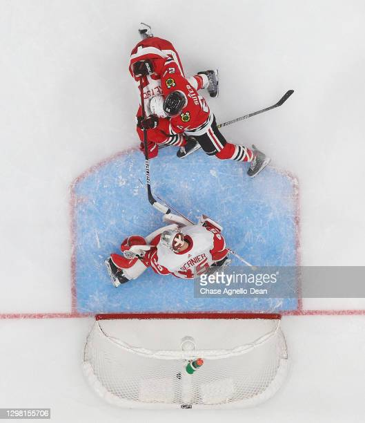 Pius Suter of the Chicago Blackhawks slides the puck past goaltender Jonathan Bernier of the Detroit Red Wings for a first period goal at the United...