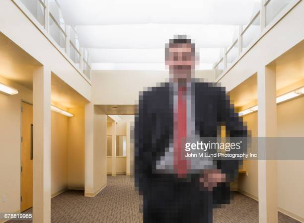 Pixelated Caucasian businessman in office corridor