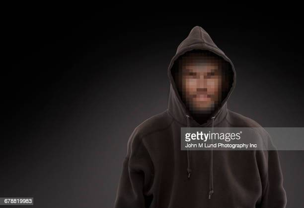pixelated face of caucasian man wearing hooded sweatshirt - hacker imagens e fotografias de stock