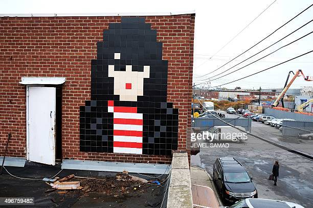 A pixelated mosaic art work by French street artist known as 'Invader' is seen on a wall of a building in New York on November 11 2015 Made famous by...