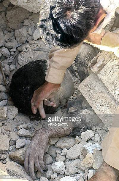 Piyush, a resident of Anjar in Bhuj district, wipes 28 Januay 2001 the face of his younger brother Kiran who was killed in the earthquake that struck...