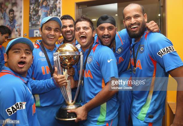 Piyush Chawla Virender Sehwag Zaheer Khan Suresh Raina Harbhajan Singh and Yusuf Pathan pose with the world cup trophy in the players dressing room...
