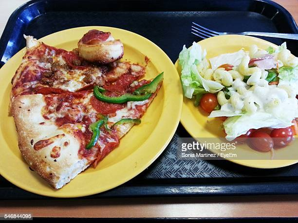 Pizza And Salad Served On Table