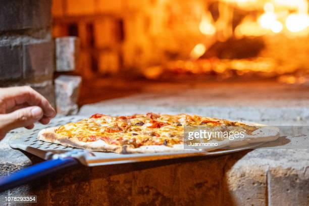 pizza being baked at a wood fire brick oven - tradition stock pictures, royalty-free photos & images