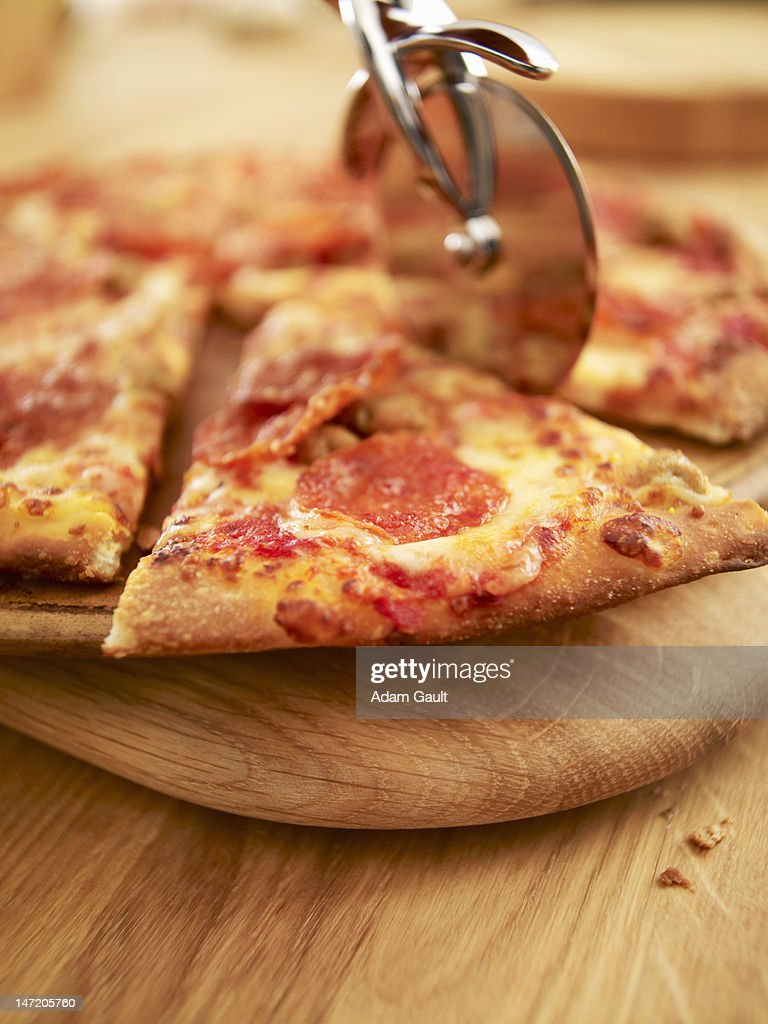Pizza being sliced : Stock Photo