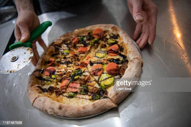 """Pizza chef Eduardo Torres Gomez slices a """"Corn of the Dead"""" vegan pizza at the Young Vegans pizza shop on January 04, 2020 in London, England...."""