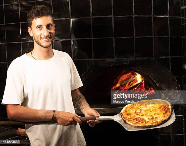 Pizza Chef holding wood fired cooked pizza