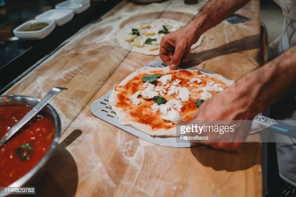 pizza chef preparing a pizza at the restaurant - naples italy stock pictures, royalty-free photos & images