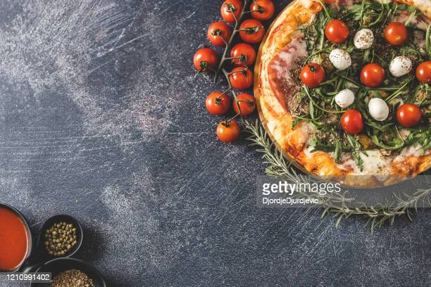 pizza, cherry tomatoes, rosemary and spices - vegetarian pizza stock pictures, royalty-free photos & images