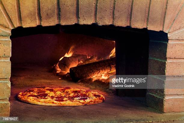 pizza cooking in stone oven - pizza oven stock photos and pictures