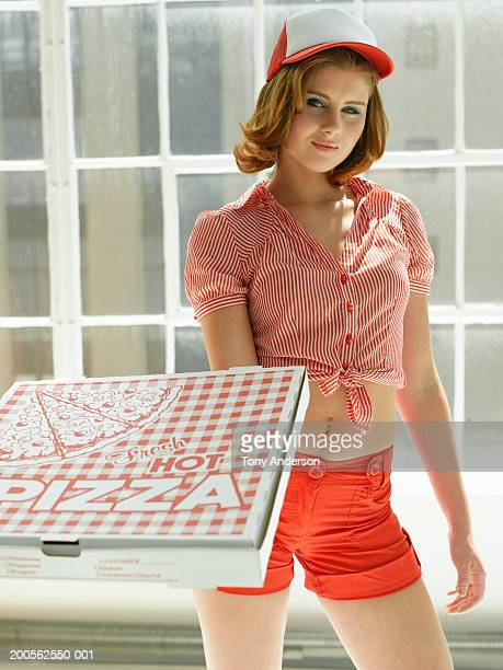 Pizza delivery girl holding out pizza box, portrait