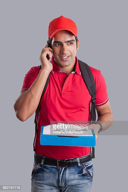 Pizza delivery man answering mobile phone against gray background