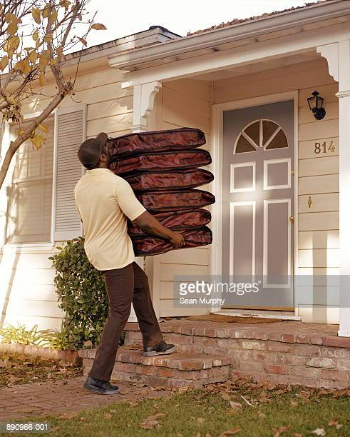 Pizza delivery man carrying six  insulated pouches in front of home