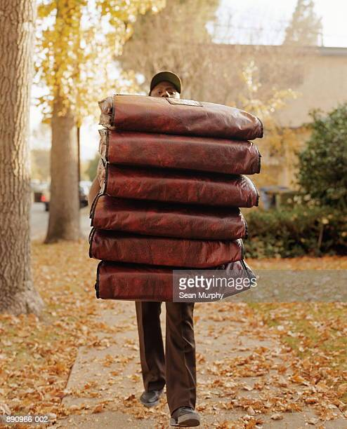 Pizza delivery man carrying six  insulated pouches