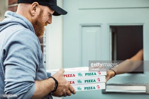 pizza delivery man delivering food to a private residence - consegna a domicilio foto e immagini stock