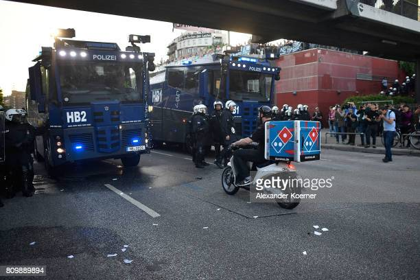 A pizza delivery man rides a scooter towards police vehicles during the 'Welcome to Hell' protest march on July 6 2017 in Hamburg Germany Leaders of...