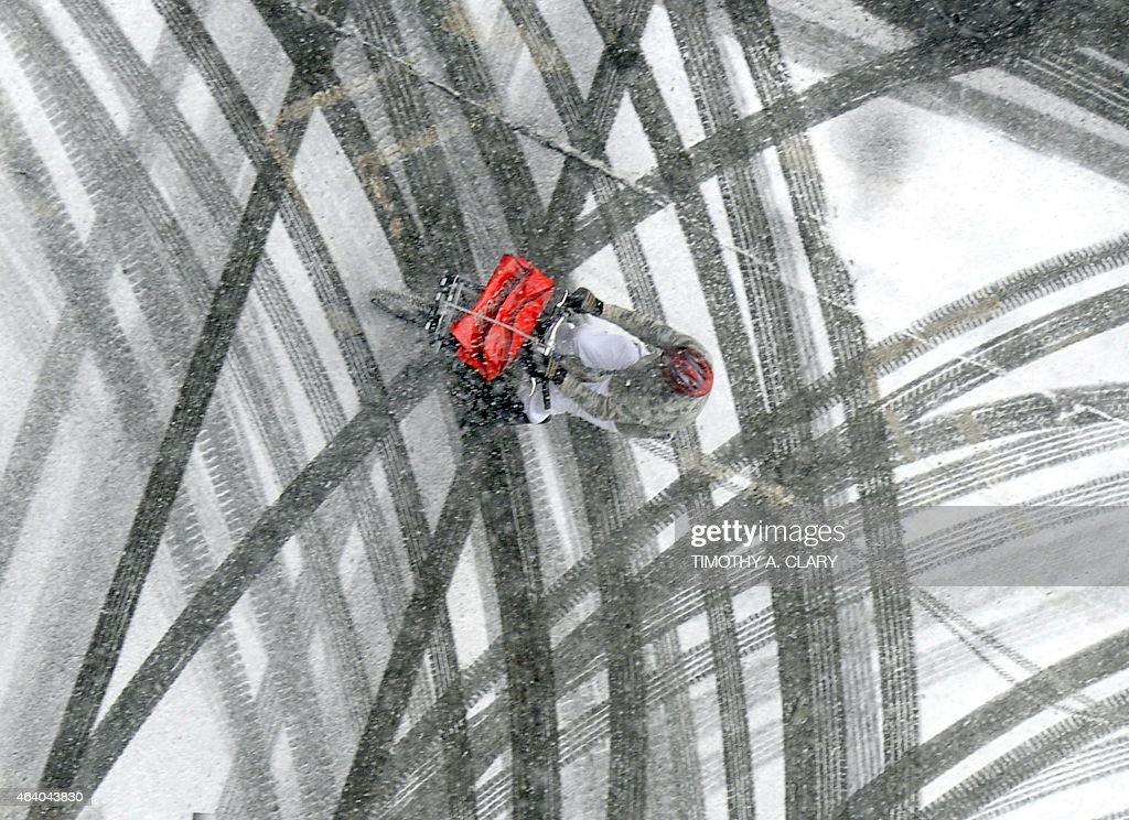 A pizza delivery man rides his bicycle through the snowy streets in Midtown Manhattan February 21, 2015 in New York. Accumulations of 1-2 inches are expected.