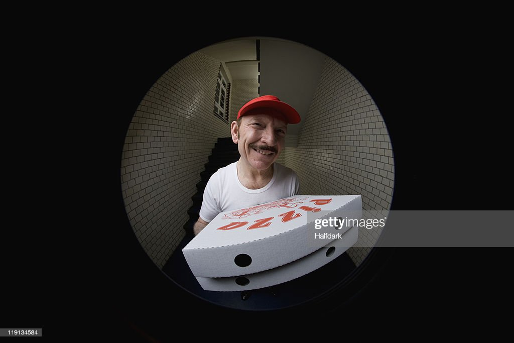 A pizza delivery man, viewed through peephole : Stock Photo
