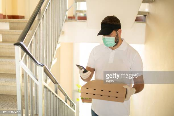 pizza delivery man with protective mask and gloves - miljko stock pictures, royalty-free photos & images