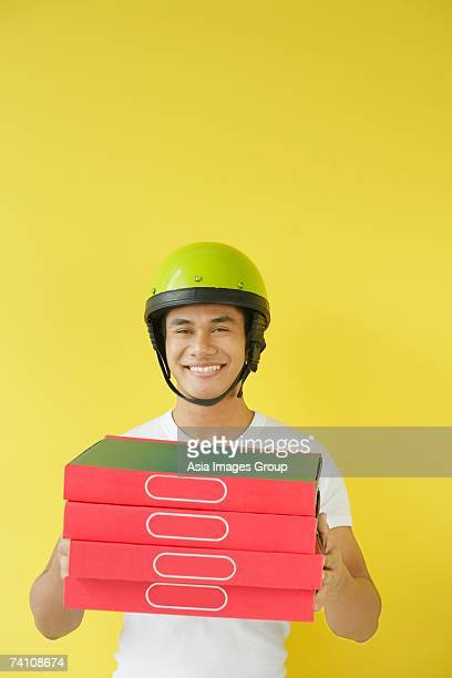 Pizza delivery person carrying a stack of pizza boxes
