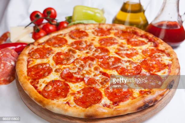 pizza diavola on a white background with ingredients around - pepperoni pizza stock photos and pictures