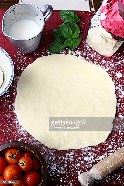 pizza dough on table rolled out