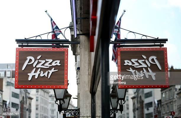 A Pizza Hut sign is reflected in a window as it hangs outside a Pizza Hut restaurant owned by Yum Brands Inc at the company's flagship restaurant on...