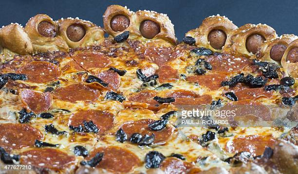 Pizza Hut's Hot Dog Bites Pizza a new belly busting pizza surrounded by 28 small hot dogs wrapped in a salted pretzel like crust is seen June 1 after...