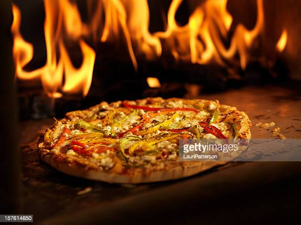 pizza in a wood burning oven - pizza oven stock photos and pictures