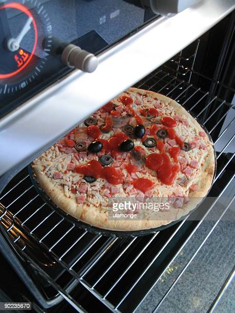 pizza in oven - pizza oven stock photos and pictures