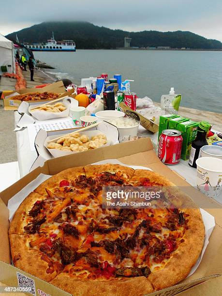 A pizza is offered at a altar for one of the missing passengers of the sunken ferry 'Sewol' prays at Jindo port on April 29 2014 in Jindogun South...