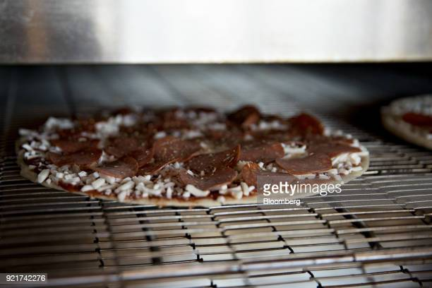 A pizza moves through an oven at a Domino's Pizza Inc restaurant in Chantilly Virginia US on Tuesday Feb 20 2018 Domino's released earnings figures...
