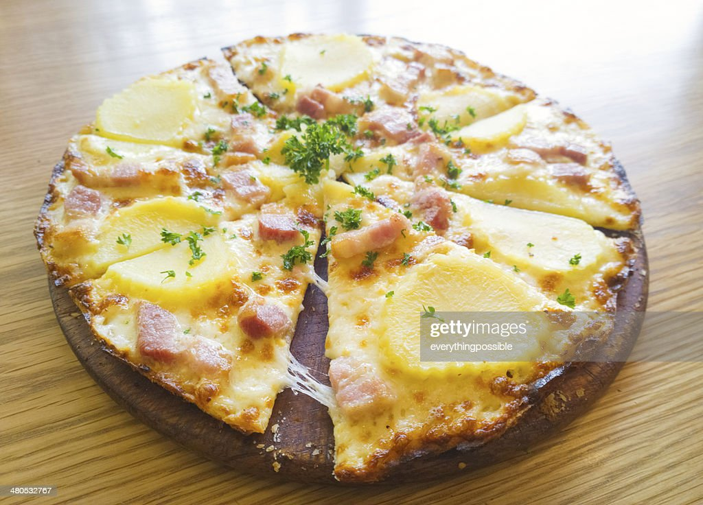 Pizza potato and ham on a wooden board : Stockfoto