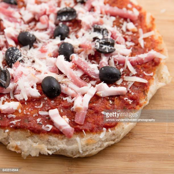 pizza preparation with lardons, black olives and parmigiano-reggiano. - black seed oil stock pictures, royalty-free photos & images