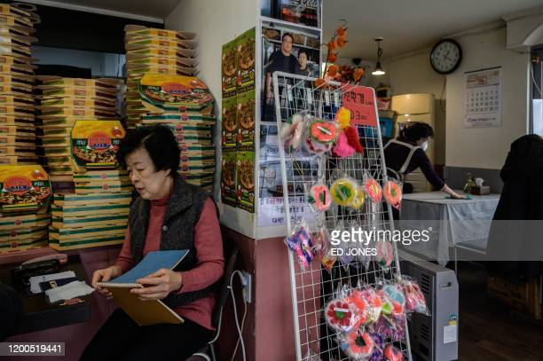 Pizza restaurant owner Eom Hangki sits before a photo of her with film director Bong Joonho in her restaurant 'Sky Pizza' in Seoul on February 13...